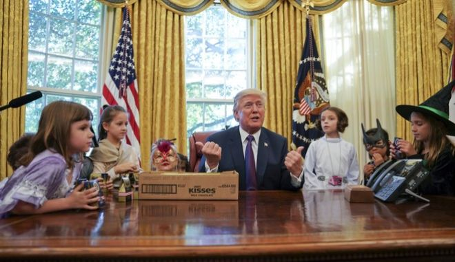 President Donald Trump meets with children dressed in their Halloween costumes in the Oval Office of the White House, Friday, Oct. 27, 2017. The White House had invited the children of members of the media to visit the president and to trick-o-treat at the White House complex of the Eisenhower Executive Office building. (AP Photo/Pablo Martinez Monsivais)