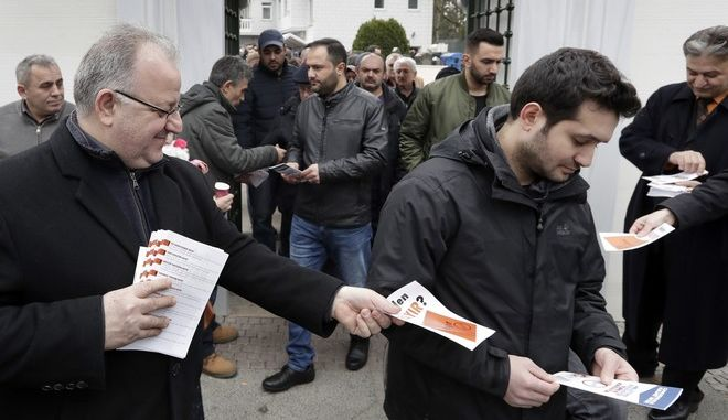 The former chairman of the Turkish community in Germany Kenan Kolat, left, hands out a contra referendum flyer to a man holding a pro referendum flyer after the Friday prayer at the Sehitlik mosque in Berlin, Germany, Friday, March 17, 2017. Turkey will hold a national referendum on April 16 on expanding the powers of Turkey's President Recep Tayyip Erdogan. (AP Photo/Michael Sohn)