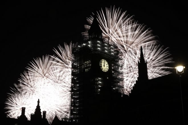 Fireworks explode over the River Thames behind the Elizabeth Tower which contains the bell know as