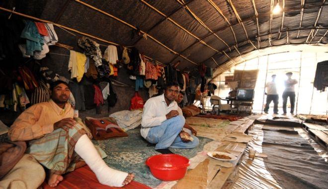 Τραυματίας μετανάστης από το Μπανγκλαντές και ομόεθνοί του σε αυτοσχέδιο κατάλυμα σε φραουλοχώραφο στη Νέα Μανωλάδα Ηλείας.   Οι χώροι στους οποίους διαμένουν οι μετανάστες εργάτες δεν ήταν ούτε για να σταβλίζονται ζώα. Η εικόνα είναι απελπιστική. Στις κατασκευές - θερμοκήπια που καλλιεργούν τις φράουλες οι ίδιες ακριβώς κατασκευές - παράγκες - θερμοκήπια αποτελούν σπίτι για τους μετανάστες εργάτες - έξω από το χωριό στα βάθη των αγρών. Πόσιμο νερό, τουαλέτα, δεν υπάρχει. Η ατομική τους υγιεινή και το μπάνιο γίνεται από σωλήνα γεώτρησης στην ύπαιθρο, με τα νερά να λιμνάζουν σε δεξαμενές ακριβώς δίπλα όπου μένουν. Στην ευρύτερη περιοχή βρίσκονται περισσότεροι από 4.500 μετανάστες που απασχολούνται κυρίως στα φραουλοχώραφα. Μετανάστες από το Μπαγκλαντές, το Πακιστάν, την Αίγυπτο, αλλά και βαλκανικές χώρες.  (EUROKINISSI/ΑΝΤΩΝΗΣ ΝΙΚΟΛΟΠΟΥΛΟΣ)