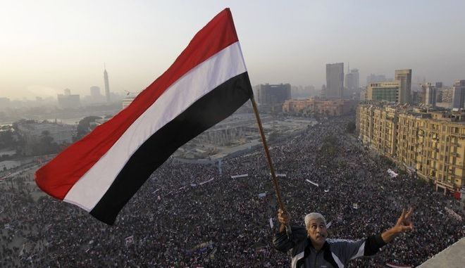 An Egyptian waves a national flag for military helicopters flying over a pro-military rally marking the third anniversary of the 2011 uprising in Tahrir Square in Cairo, Egypt, Saturday, Jan. 25, 2014. Egyptian riot police have fired tear gas to disperse hundreds of supporters of ousted Islamist President Mohammed Morsi protesting as the country marks the third anniversary of the 2011 uprising, as supporters of the military gathered in rival rallies in other parts of the capital, many of them urging military chief Gen. Abdel-Fattah el-Sissi, the man who removed Morsi, to run for president. (AP Photo/Amr Nabil)