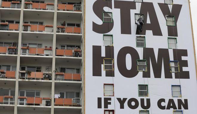 """Πανό σε πολυκατοικία που γράφει """"Μείνετε Σπίτι"""", Αφρική"""