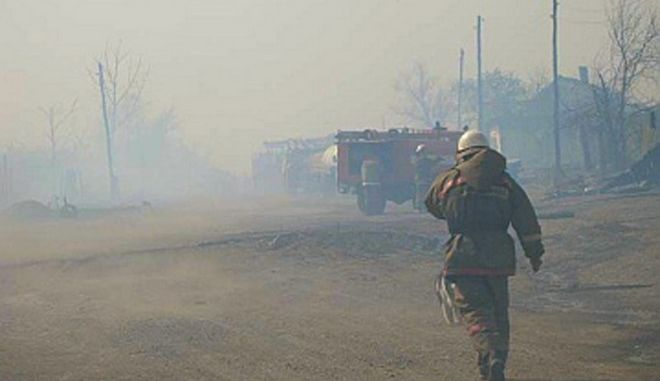 In this undated photo taken from the Website of the Ministry for Emergency Situations, Khakassia branch Monday, April 13, 2015, a firefighter walks through smoke from the fire in Khakassia, a region in southeastern Siberia, Russia. Russian authorities say out-of-control agricultural fires have killed at least 15 people, injured hundreds more and destroyed or damaged more than 1,000 homes in Siberia. The fires were started by farmers burning the grass in their fields, but spread quickly because of strong winds. (Ministry for Emergency Situations, Khakassia branch in Siberia via AP)
