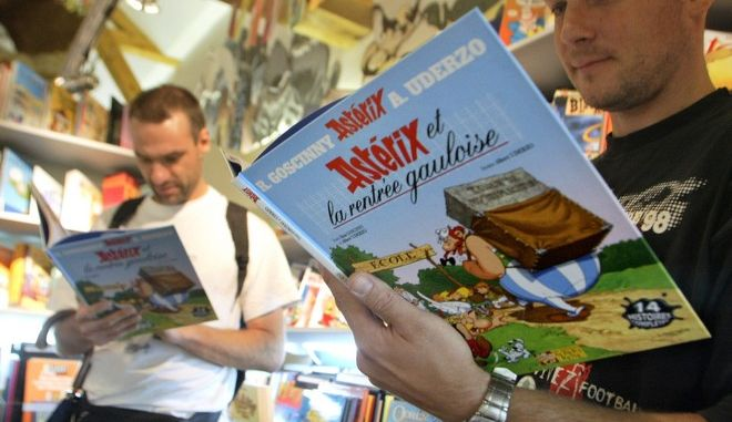 """Fans read the last Asterix album """" Asterix et la rentree Gauloise"""" (Asterix and the Gallic's return) by France's popular cartoon authors Uderzo and Goscinny, Friday Aug. 29, 2003.The new 56-pages album released Friday, features 14 of the Gallic hero's exploits over the past four decades.(AP Photo/Franck Prevel)"""