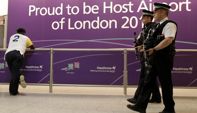 Airport police patrol the arrival area of Terminal 4 at Heathrow Airport in London Monday, July 16, 2012 as the London prepares for the 2012 Summer Olympics.  Competitors are arriving in London during preparations for the upcoming London 2012 Olympic Games.(AP Photo/Charlie Riedel)