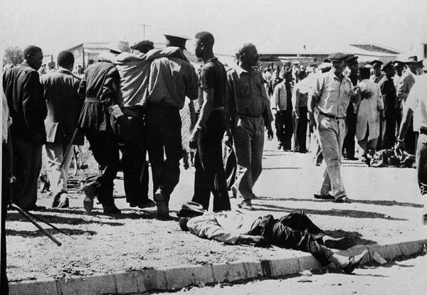 A South African man lies on the ground near police who fired on demonstrators protesting against apartheid in Sharpeville, March 21, 1960. (AP Photo)