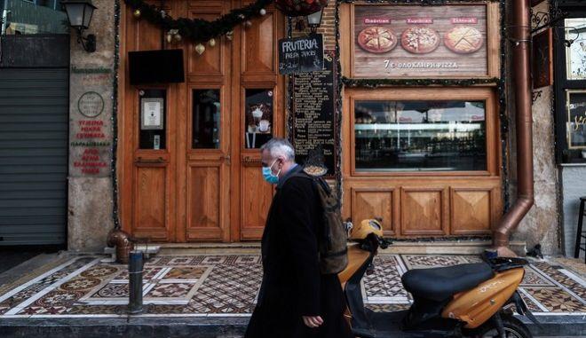 Άνθρωπος με μάσκα μπροστά από κλειστό κατάστημα στο κέντρο της Αθήνας