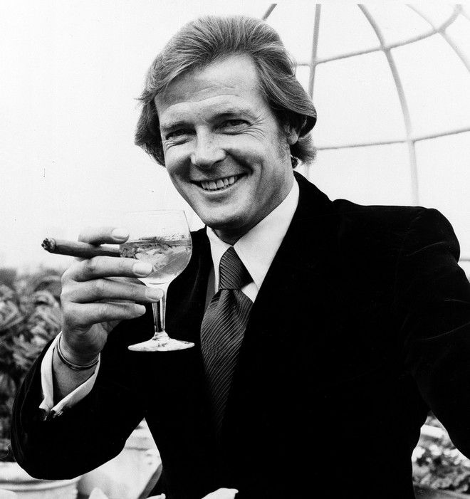 Actor Roger Moore poses with a martini and a big cigar at the Dorchester Hotel in London, on August 1, 1972, after the announcement was made that he will play the British secret agent James Bond 007, in the new production