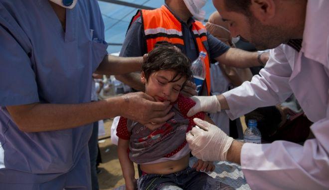 Γιατροί εξετάζουν ένα παιδί μετά την επίθεση του ισραηλινού στρατού με χημικά κατά Παλαιστινίων που διαδήλωναν στη λωρίδα της Γάζας με αφορμή τα εγκαίνια της πρεσβείας των ΗΠΑ στην Ιερουσαλήμ