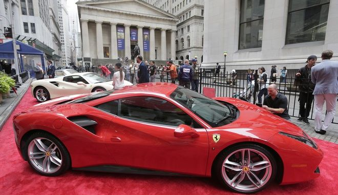 Ferraris are lined up in front of the New York Stock Exchange, Monday, Oct. 9, 2017. Ferrari is celebrating its 70th anniversary. (AP Photo/Seth Wenig)