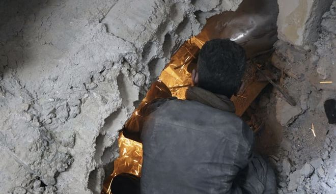 This photo released by the Syrian Civil Defense White Helmets, which has been authenticated based on its contents and other AP reporting, shows a member of the Syrian Civil Defense group searching for victims under the rubble of a destroyed building after airstrikes and shelling hit in Ghouta, a suburb of Damascus, Syria, Wednesday, March. 7, 2018. Government forces carried out punishing airstrikes against an opposition-held suburb of Damascus, seeking to divide the besieged enclave in two and further squeeze rebels and tens of thousands of civilians trapped inside, state-run media and opposition activists reported. (Syrian Civil Defense White Helmets via AP)