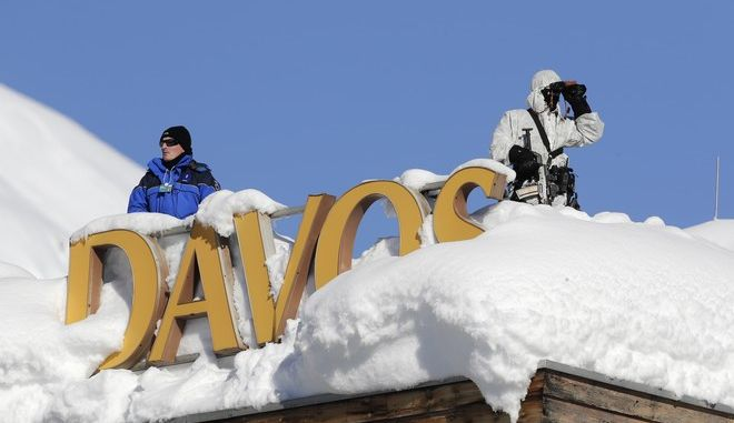 Armed Swiss police officers stand guard on the roof of a hotel near the congress center where the annual meeting of the World Economic Forum take place in Davos, Switzerland, Tuesday, Jan. 23, 2018. (AP Photo/Markus Schreiber)