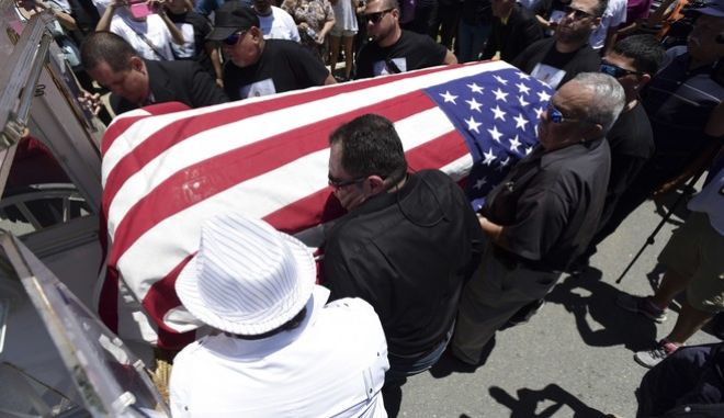 Family and friends carry the flag draped coffin of Angel Candelario Padro, a 28-year-old nurse and National Guard member, as he is put to rest at the Guanica municipal cemetery in Puerto Rico, Saturday, June 18, 2016. Angel Candelario Padro was one of 49 persons slain in the mass shooting at a nightclub in Orlando, Fla. The ceremony for Candelario was one of several being held on the island this week for victims of the Orlando attack. (AP Photo/Carlos Giusti)