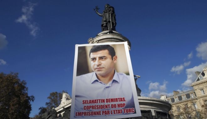 Kurdish demonstrators hold a portrait of pro-Kurdish Peoples' Democratic Party (HDP) leader Selahattin Demirtas during a rally to protest against Turkish President Recep Tayyip Erdogan, at Republique Square in Paris, Saturday, Nov. 5, 2016. Authorities in Turkey detained 11 pro-Kurdish Peoples' Democratic Party (HDP) lawmakers early Friday as part of ongoing terror-related investigations, including both party co-chairs Selahattin Demirtas and Figen Yuksekdag and other senior officials, the Interior Ministry said. (AP Photo/Francois Mori)