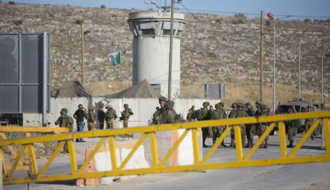 Israeli soldiers and security forces stand at a checkpoint near the West Bank city of Nablus, Friday, June 10, 2016, after a Palestinian attempted a stabbing attack. Palestinian was shot and wounded, army said. (AP Photo/Majdi Mohammed)