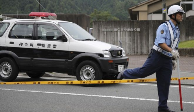 A police officer walks over a police line tape in front of the gate to Tsukui Yamayuri-en, a facility for the handicapped where a number of people were killed and dozens injured in a knife attack in Sagamihara, outside Tokyo Tuesday, July 26, 2016.  Police said they responded to a call about 2:30 a.m. Tuesday from an employee saying something horrible was happening at the facility. A man turned himself in at a police station about two hours later, police said. (AP Photo/Eugene Hoshiko)