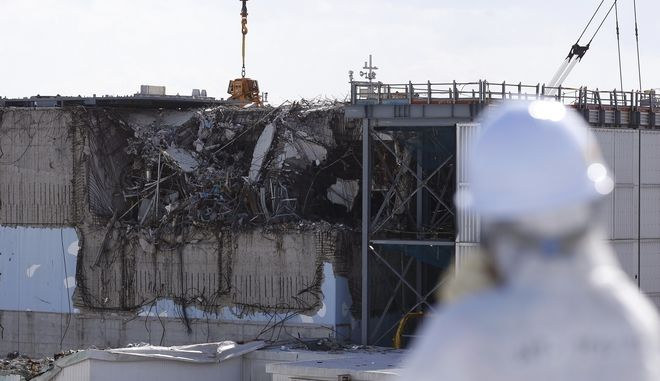 A member of the media tour group wearing a protective suit and a mask looks at the No. 3 reactor building at Tokyo Electric Power Co's (TEPCO) tsunami-crippled Fukushima Dai-ichi nuclear power plant in Okuma, Fukushima Prefecture, northeastern Japan, Wednesday, Feb. 10, 2016. In one month, Japan is marking the fifth anniversary of a devastating earthquake and tsunami that hit on March 11, 2011 and left nearly 19,000 people dead or missing, turned coastal communities into wasteland and triggered a nuclear crisis. (Toru Hanai/Pool Photo via AP)