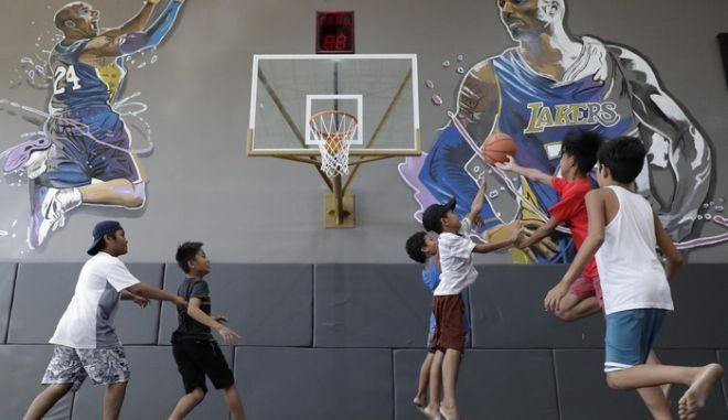 Παιδιά παίζουν μπάσκετ στις Φιλιππίνες σε γήπεδο που απεικονίζει τον Kobe Bryant