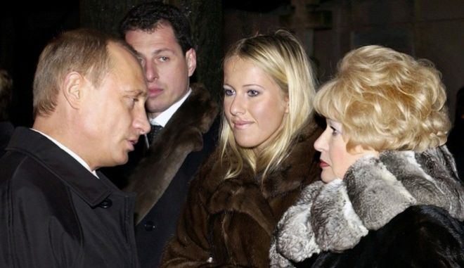 """FILE - In this Saturday, Nov. 29, 2003 file photo, Russian President Vladimir Putin, left, speaks with Lyudmila Narusova, right, widow of former St. Petersburg mayor Anatoly Sobchak, and Sobchak's daughter Ksenia, as he visited the grave of Anatoly Sobchak at a cemetery in St. Petersburg, Russia. Ksenia Sobchak, the 30-year-old blond socialite and TV personality said """"I'm Ksenia Sobchak, and I've got something to lose. But I'm here."""" when she began her unlikely foray into political activism by taking the stage at a huge anti-Putin rally in December. Russian President Vladimir Putin. (Sputnik, Government Pool Photo via AP, file)"""