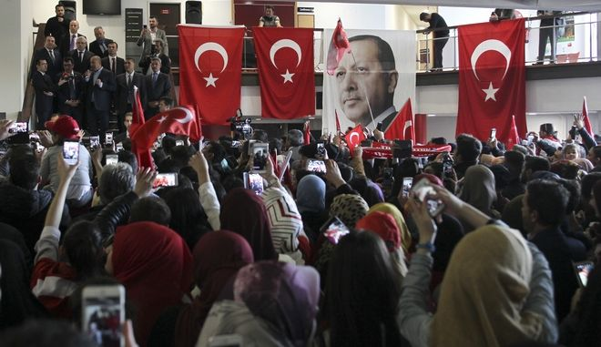 The pictures of Turkey's President Recep Tayyip Erdogan hangs on a balustrade among Turkish flags as Turkish Foreign Minister Mevlut Cavusoglu, center left, speaks during a campaign gathering in Metz, eastern France, Sunday, March 12, 2017. Foreign Minister Mevlut Cavusoglu was in France Sunday to whip up support for controversial constitutional reforms to expand the powers of the Turkish presidency. (AP Photo/Elyxandro Cegarra)