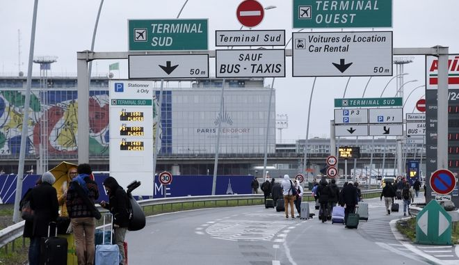 Travellers walk on the highway to the Orly airport, south of Paris, Saturday, March, 18, 2017. A man was shot to death Saturday after trying to seize the weapon of a soldier guarding Paris' Orly Airport, prompting a partial evacuation of the terminal, police said. (AP Photo/Thibault Camus)