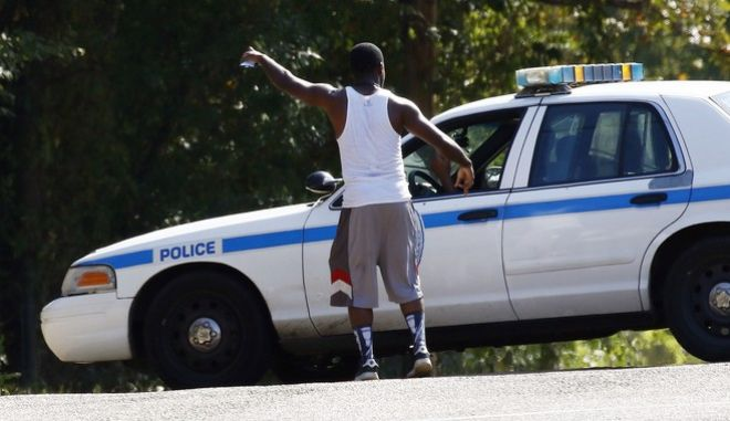 A resident gestures to a policeman as a police presence remains in a south Jackson, Miss., neighborhood, Thursday, Sept. 22, 2016, while lawmen continue to negotiate with a man suspected of holding about a dozen people against their will. Authorities believe all the hostages have been safely removed without a shot being fired, but the person suspected of holding the hostages remained inside a Mississippi boarding house. (AP Photo/Rogelio V. Solis)