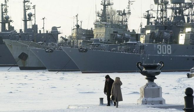 A couple walks past Russian Navy ships caught in the ice at a military base in Kronstadt, near St.Petersburg, Russia, Saturday, Jan. 11, 2003. The deep freeze has slowed traffic in St. Petersburg's port as scores of ships wait for icebreakers to slam through ice up to a meter (3.5 feet) deep. Temperatures dropped as low as -29 C (-20 F). (AP Photo/Dmitry Lovetsky)