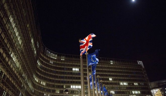 The British and EU flags flap in the wind outside EU headquarters in Brussels on Friday, Dec. 8, 2017. British Prime Minister Theresa May, met with European Commission President Jean-Claude Juncker early Friday morning following crucial overnight talks on the issue of the Irish border. (AP Photo/Virginia Mayo)