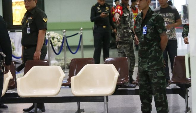A Thai soldier stands guard as police officers investigate the lobby of Phramongkutklao Hospital, a military-owned hospital that is also open to civilians, in Bangkok after a bomb wounded more than 20 people, in Bangkok Monday, May 22, 2017. The deputy commissioner of the Royal Thai Police said investigators found traces of batteries and wires at the scene Monday. (AP Photo/Sakchai Lalit)