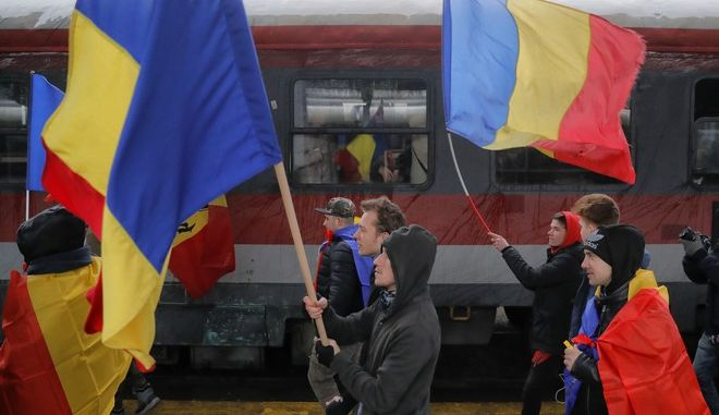 Protesters hold Romanian flags to welcome protesters arriving from the western town of Timisoara, at the Gara de Nord, the main railway station in Bucharest, Romania, Saturday, Jan. 20, 2018. Romanians, many traveling from across the country, joined a protest in the Romanian capital against high level corruption and planned modifications to the legal system they say will hamper prosecutions. (AP Photo/Vadim Ghirda)
