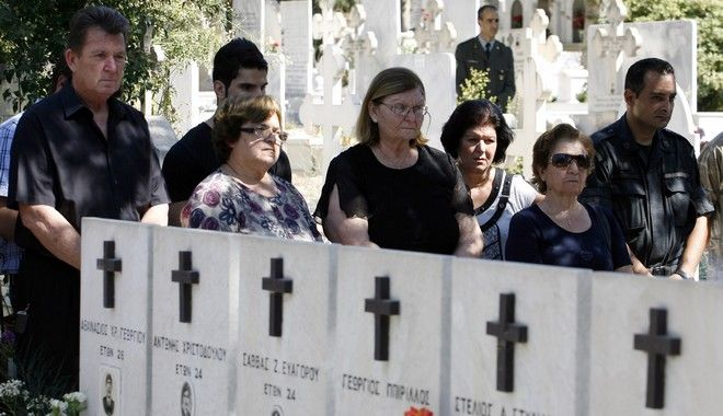 Cypriot people stand by the graves of Cypriot soldiers and police officers killed July 15, 1974, during a coup which was intended to overthrow Archbishop Makarios, at the Ayios Constantinos and Elenis cemetery in the capital of Nicosia, Cyprus, Sunday, July 15, 2012. Cyprus was split into Greek Cypriot south and Turkish Cypriot north in 1974 when Turkey invaded in response to a coup by supporters of unification with Greece. (AP Photo/Philippos Christou)