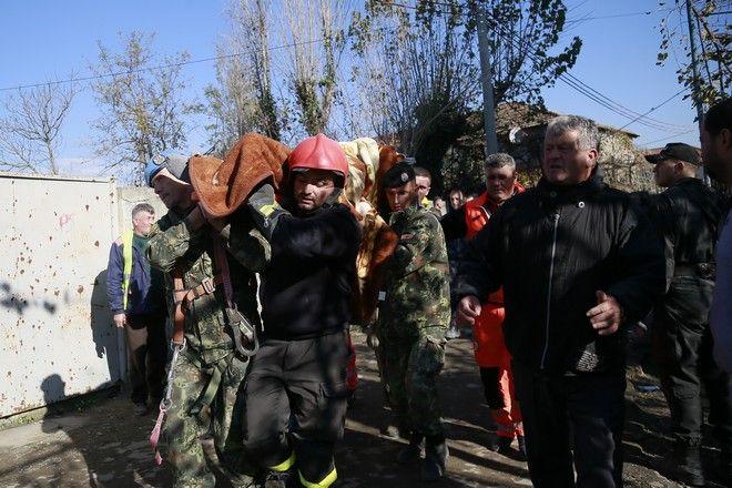 Διασώστες μεταφέρουν τραυματισμένη γυναίκα που μόλις έχει απεγκλωβιστεί από τα ερείπια
