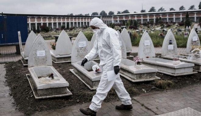 Άντρας με φόρμα προστασίας σε νεκροταφείο στο Τορίνο