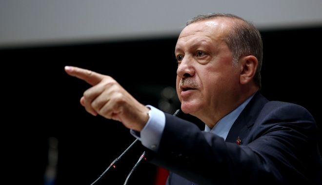 Turkey's President Recep Tayyip Erdogan, gestures as he delivers a speech during a ceremony to rejoin the ruling Justice and Development Party, or AKP, in Ankara, Turkey, Tuesday, May 2, 2017. Erdogan rejoined the Islamic-rooted party he co-founded in a ceremony on Tuesday, following his narrow victory in a referendum that expands the powers of the president's office. (Press Presidency Press Service via AP, Pool)