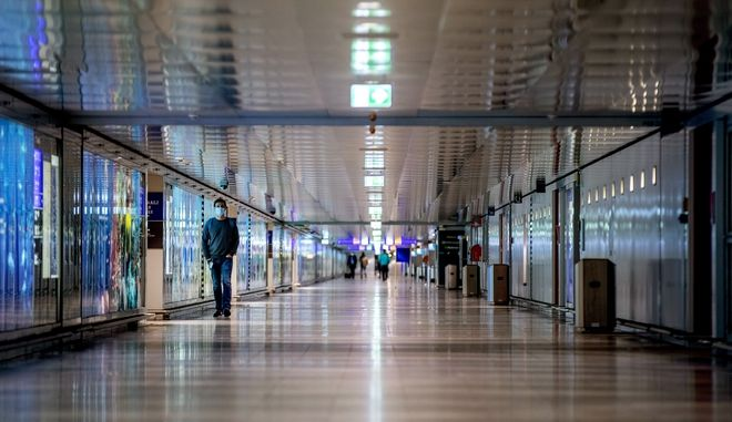 A man walks through a terminal at the international airport in Frankfurt, Germany, Tuesday, Jan. 26, 2021. German government increased the border controls for some flights coming in to avoid the outspread of the coronavirus. (AP Photo/Michael Probst)