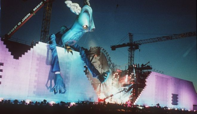 BER101. Berlin. In front of the Reichstag, the pre-war parliament building, a giant rubber puppet peers over the artificial bricks during the performance of 'the Wall' at East Berlin, Germany 22.July 1990 evening. (AP Photo /Jockel Finck)