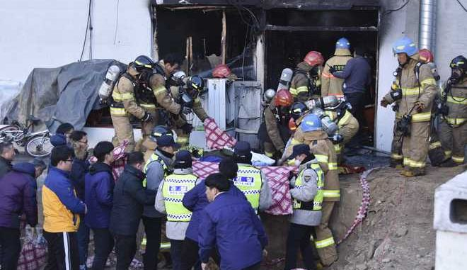 Rescue teams remove bodies from a hospital fire in Miryang, South Korea, Friday, Jan. 26, 2018.  A fire swept through the hospital in southeastern South Korea on Friday, killing more than 30 people and injuring dozens in one of the country's most deadly fires in recent years. (Kim Gu Yeon/Gyeongnam Domin Ilbo via AP)