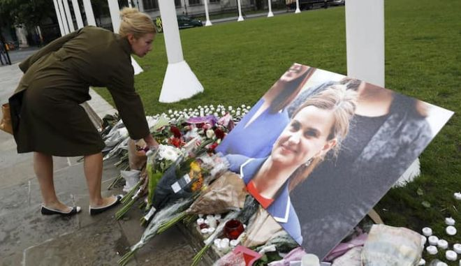 A woman leaves a floral tribute next to a photograph of murdered Labour Member of Parliament Jo Cox in Parliament Square, London, Britain June 17, 2016  REUTERS/Stefan Wermuth