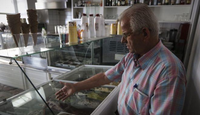 Καταστηματάρχης δείχνει τα παγωτά στο ψυγείο της επιχείρησής του στην πόλη της Ύδρας το πρωΐ της Δευτέρας 27 Αυγούστου 2018.