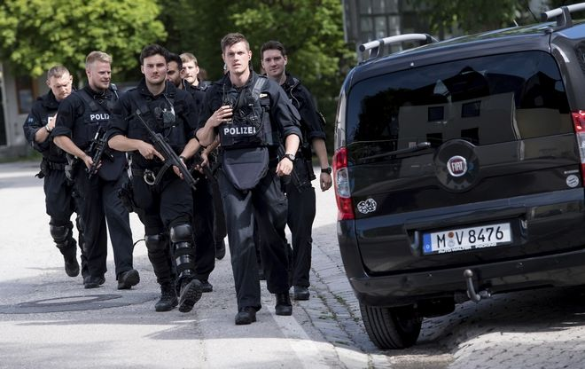Policemen  arrive at  a subway station in Munich, Germany, Tuesday, June 13, 2017.  Several people were injured, including a police officer, in a shooting early Tuesday at a Munich subway station, police said. Munich police said in a tweet that the policewoman's injuries were serious. The suspect was also injured and is in custody. The shooting occurred during a morning police check at the Unterfoehring subway station, Munich police spokesman Michael Riehlein said. (Sven Hoppe/dpa via AP)