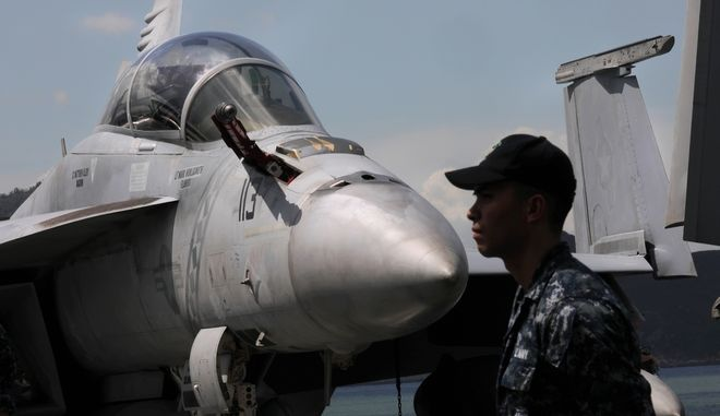 A U.S. Navy serviceman stands guard on the flight deck of the USS Ronald Reagan aircraft carrier in Hong Kong, Monday, Oct. 2, 2017. A senior U.S. Navy commander of the nuclear powered aircraft carrier reportedly participating in joint drills with South Korea later this month told reporters during a stop in Hong Kong on Monday that his strike group is committed to defending U.S. allies in the region.  (AP Photo/Vincent Yu)