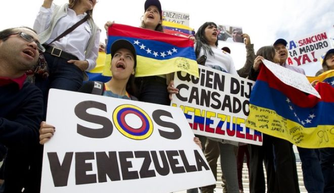 Demonstrators who are against the Venezuelan government chant outside of the Organization of American States (OAS) during the special meeting of the Permanent Council, in Washington, Monday, April 3, 2017, to consider the recent events in Venezuela. (AP Photo/Jose Luis Magana)