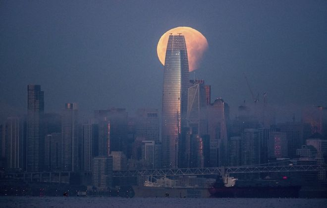 A partially-eclipsed super blue blood moon sets behind the Salesforce Tower on Wednesday, Jan. 31, 2018, in San Francisco. It's the first time in 35 years a blue moon has synced up with a supermoon and a total lunar eclipse, also called a blood moon because of its red hue. (AP Photo/Noah Berger)
