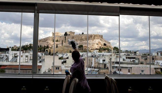 Γυναίκα καθαρίζει τα τζάμια εστιατορίου στο κέντρο της Αθήνας, που έχει θέα την Ακρόπολη