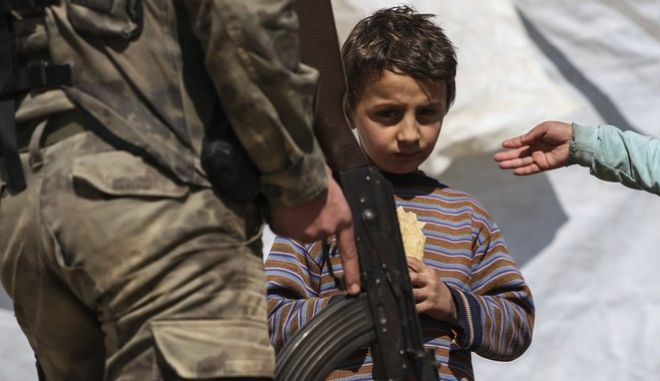 A Syrian child looks on as a Turkey-backed opposition fighter of the Free Syrian Army secures the streets of the northwestern city of Azaz, Syria, during a Turkish government-organised media tour into northern Syria, Saturday, March 3, 2018. Already in the sixth week of its offensive on the Kurdish-held enclave of Afrin in northwestern Syria, Turkey wants to oust the Syrian Kurdish People's Protection Units, or YPG, from Afrin. It considers the group an extension of a Kurdish insurgency within its own borders.(AP Photo/Emrah Gurel)