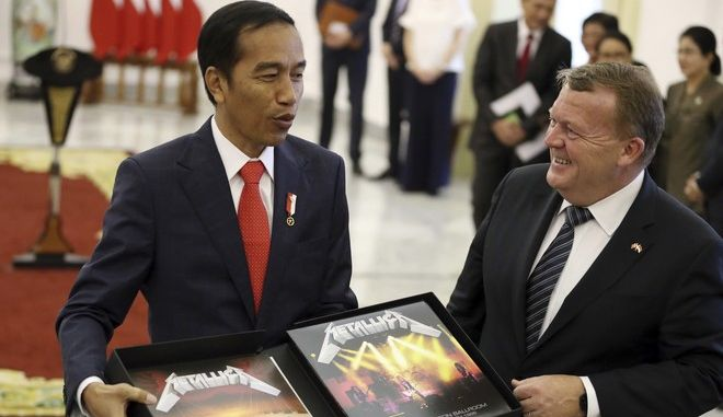 Indonesian President Joko Widodo, left, reacts as Denmark's Prime Minister Lars Lokke Rasmussen presents a box of Metallica's vinyl records autographed by its Danish member Lars Ulrich as a souvenir during their meeting at the presidential palace in Bogor, West Java, Indonesia, Tuesday, Nov. 28, 2017. Rasmussen is currently on a three-day visit in the country. (AP Photo/Dita Alangkara)