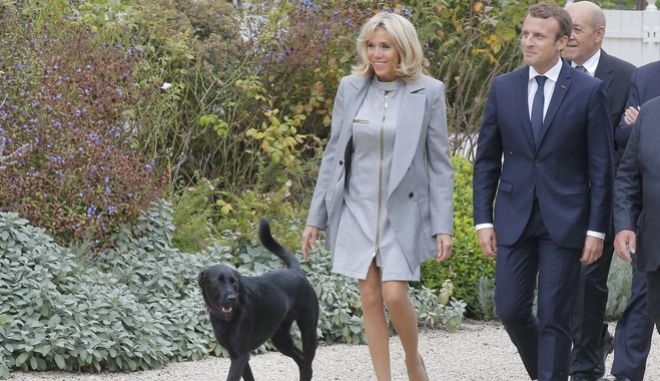 French President Emmanuel Macron, right, and his wife Brigitte Macron arrive with their dog called Nemo for a group photo with invited chefs during an event at the Elysee Palace in Paris, Wednesday, Sept. 27, 2017. 180 top chefs were invited to the Elysee Palace to promote the French cuisine. Bodyguard left. (AP Photo/Michel Euler, Pool)