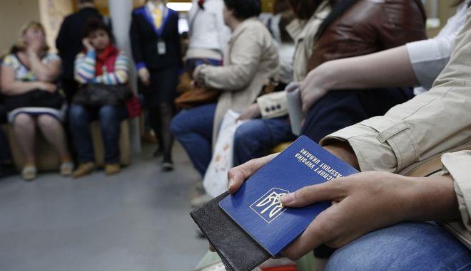 "Ukrainians wait for documents to obtain a international passport in the passport service of the State Enterprise ""Document"" in Kiev, Ukraine, Wednesday, May 17, 2017. The regulation on the EU visa liberalisation for Ukrainian citizens has been signed in Strasbourg on Wednesday.(AP Photo/Sergei Chuzavkov)"