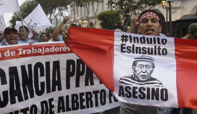 """Demonstrators shout slogans against the pardon of former President Alberto Fujimori while holding the flag of Peru that reads in Spanish: """"Pardon is Insult, Assassin"""", in Lima, Peru, Thursday, Dec. 28, 2017. Peru's President Pedro Pablo Kuczynski granted a medical pardon to the former strongman Fujimori who was serving a 25-year sentence for human rights abuses, corruption and the sanctioning of death squads. (AP Photo/Martin Mejia)"""