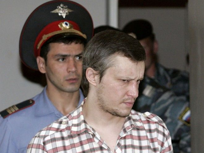"""Alexander Pichushkin is followed by a policeman as he enters the courtroom for preliminary hearings at a Moscow court August 13, 2007. Investigators now believe the """"Bitsa maniac,"""" who claims he killed to fill squares on an imaginary chessboard, may have murdered 62 people, 10 more than previously thought, an Interior Ministry official said as RIA Novosti agency reported.  REUTERS/Alexander Natruskin  (RUSSIA) - RTR1SQMZ"""